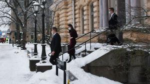 Tre personer går nerför trappan utanför Borgå stadshus. Det är Sanna Marin samt hennes säkerhetsvakt och assistent.
