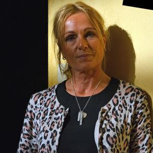 Rektor Anna Magnusson, Tullgårdsskolan i Stockholm, står vid gul vägg med #nivetingenting i hörnet