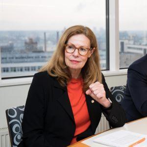 Birgitte Bonnesen vd på Swedbank sitter vid ett bord med papper framför sig.