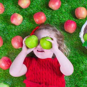 En flicka omringad av gröna och röda äppel.