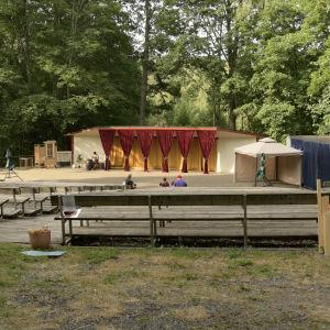 En utomhusteater i ett lummigt område. Sommar. Bänkar som är tomma, scenen är också tom. Ingen föreställning.