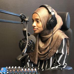 Amal Said har hörlurar och sitter framför en mikrofon i en poddstudio.