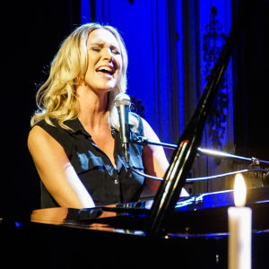 Sanna Nielsen vid en svart flygel med levande ljus i förgrunden.