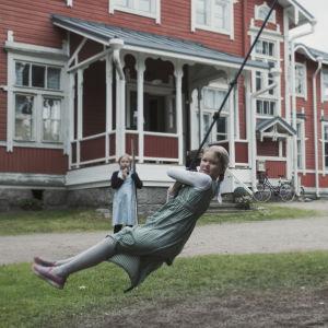 Barn leker på skolgård. En flicka har styltor, andra snurrar i en snurrgunga.
