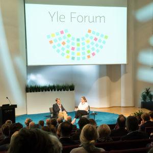 Toimittajat istumassa tuoleilla, etualalla yleisöä, taustaseinällä Yle Forumin tunnusjuliste