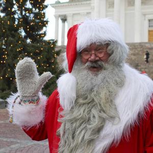 Julgubben vinkar framför en stor julgran och domkyrkan i Helsingfors.