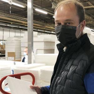 Bild på Peter Nordlund, iklädd svart munskydd tillverkat i hans fabrik. Han håller i ett kassettfilter och står inne i den fabrikshall som tillverkar dem.