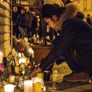 En person hukar vid ett gatuhörn fyllt av ljus.