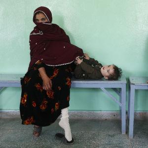Två kvinnor sitter på en bänk i ett sjukhus med sina barn.