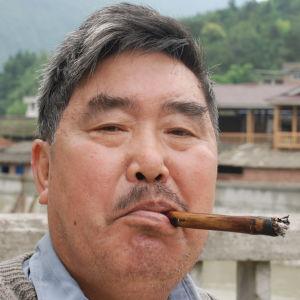 Kinesisk man röker cigarett med ett munstycke av bambu.