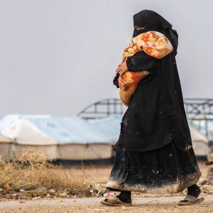 En kvinna i niqab med ett barn i famnen promenerar med vita tält i bakgrunden.