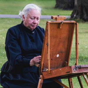Valkohiuksinen nainen mustassa pitkässä mekossa istuu maalaustelineen ääressä puistossa.