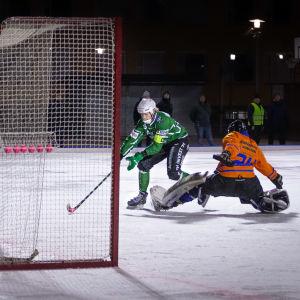 En målvakt i orange skjorta försöker hindra en bandyspelare i grönt från att skjuta i mål.