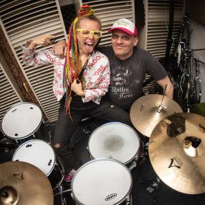 Vicky Österberg med färglada dreadlocks framför trummor tillsammans med Lasse Grönroos.