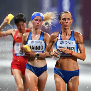 Alisa Vainio, Anne-Mari Hyryläinen och två andra maratonlöpare springer och förser sig med vatten samtidigt.
