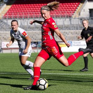 Fotbollsspelaren Ida Adamsson i beredskap att sparka bollen under en match.