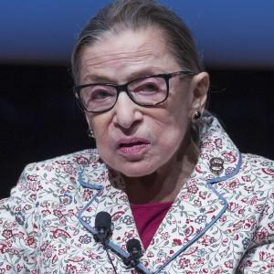 Ruth Bader Ginsburg sitter i en soffa med knappmikrofon på en blommig kavaj.