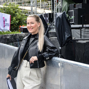 Leende kvinna i läderjacka står lutat mot en scenkant.