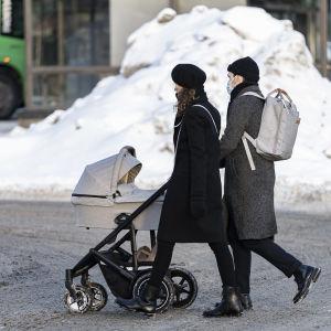Pariskunta työntää lastenvaunuja tienyli Hakaniemen Torilla kasvomaskit kasvoilla.