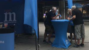 Tre personer diskuterar vid ett bord med Moderaternas logo.