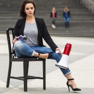Kvinna sitter på en kökstol ute på en plaza, med en megafon i handen.