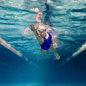 En kvinna simmar i en simbassäng. Bilden är tagen under vattnet.