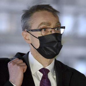 Tuomas Pöysti går med ett svart munskydd på. Han håller i remmen till en axelväska som vilar på axeln.