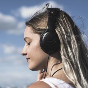 En kvinna lyssnar på något i hörlurar.