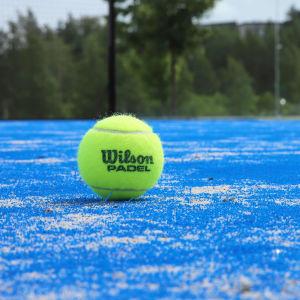 En gul boll på en blå padeltennisbana.