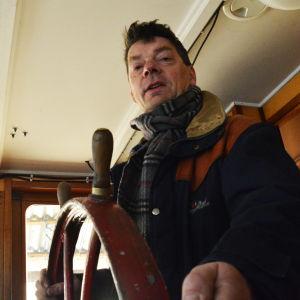 En medelålders man står i en kajuta och håller i ett roder av trä. Bilden är tagen nerifrån och mannen tittar in i kameran.