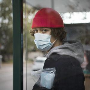 En kille som bär munskydd står invid en busshållplats.
