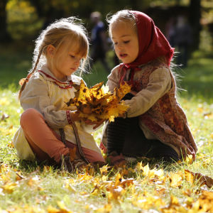 Flickor leker med höstlöv.