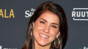 En glad kvinna med mörkt axellångt hår och stora runda örhängen i guldfärg tittar in i kameran.