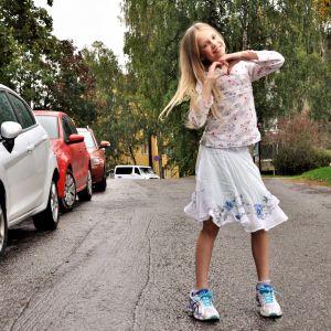 Ida Mansikka står mitt på en landsväg och tittar in i kameran. Hon har en blommig skjorta och en vit klänning på sig, hon ler in i kameran och formar ett hjärta med händerna. Ute är det regnigt väder.