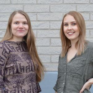 Två unga kvinnor står framför en vit tegelvägg.