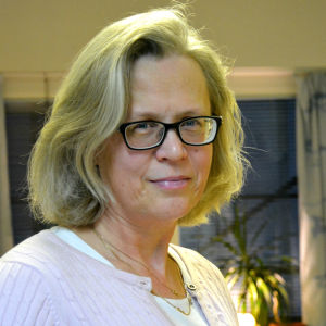 en kvinna i ljust hår och ljusa kläder och mörka glasögon står mitt i ett kontorsrum