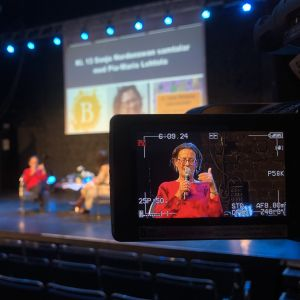 En kvinna syns i en ruta på en filmkamera. I bakgrunden syns kvinnan sitta på en scen och samtala med en annan kvinna.