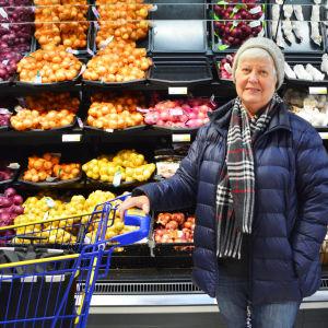 En äldre kvinna står med en kundvagn framför en hylla med lök i en matbutik.