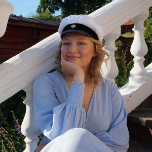Elin Stråhlmann sitter i trädgården med studentmössan på.