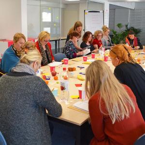 Flera människor sitter inomhus runt ett långt bord. De har papper framför sig som många av dem läser eller skriver på.