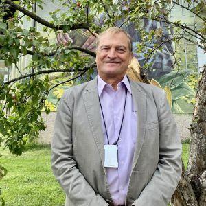 En äldre man står framför ett träd och tittar in i kameran.
