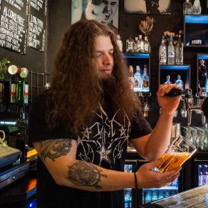 Baarimestari Samuel Honkavaara kaataa olutta lasiin The Riff baarissa.