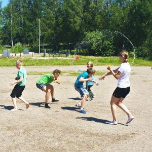 Barn på en sandplan kastar vattenballonger på varandra.