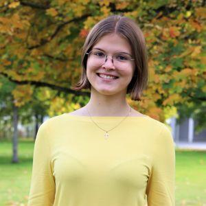 Isabel Rautamo ler in i kameran. Höstlöv i bakgrunden.
