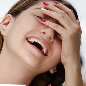 Flicka som skrattar med handen framför ansiktet.