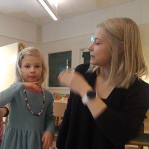 """Liv Leopold och Alexandra Östergård visar tecknet för """"mamma""""."""