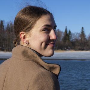 Ung kvinna står vid smältande vattendrag, ler över axeln.