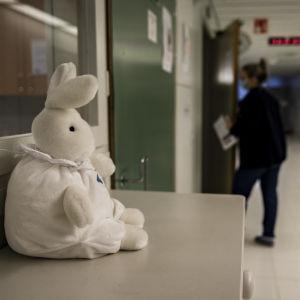 Oulun yliopistonsairaalassa lastenlelu katselee käytävään päin missä hoitaja kävelee