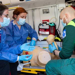 Kätilöt Hanna-Mari Huttunen ja Lea Hiltunen opastavat ensihoitajaa synnytys-simulaatiossa jossa lapsi on syntymässä.