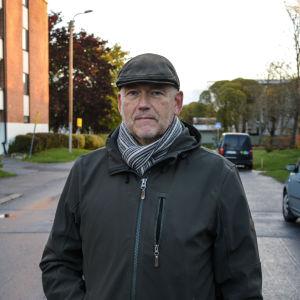 Medelålders man iklädd keps, jacka och halsduk står på gata och tittar in i kameran.